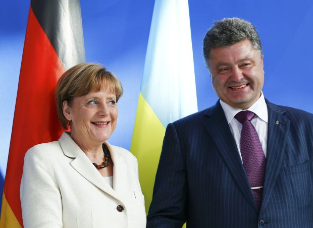 Ukrainian president-elect Poroshenko and German Chancellor Merkel smile as they address the media before a meeting at the Chancellery in Berlin